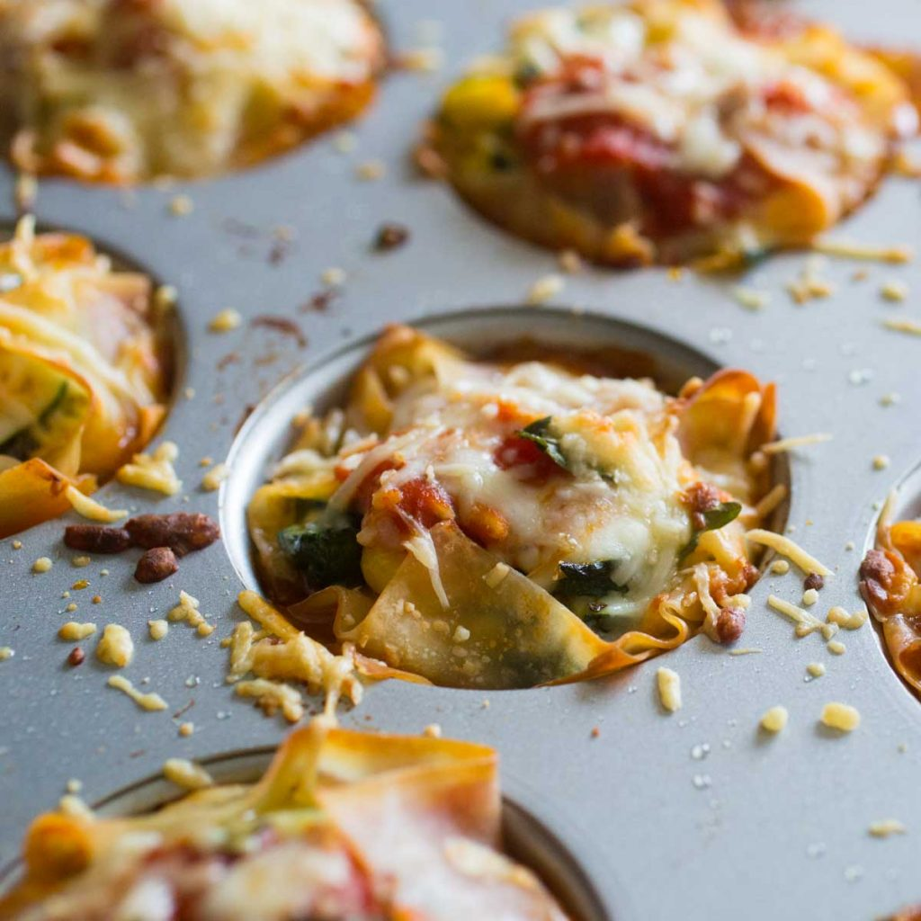 A muffin tin filled with garden lasagna cupcakes shows the spinach and tomatoes covered in melted cheese.
