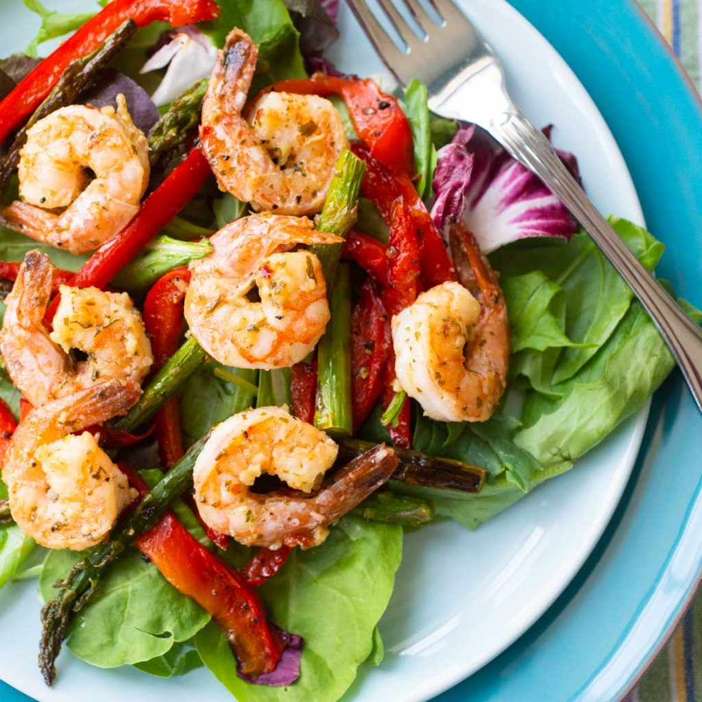 A blue plate has a bed of lettuce topped with lemon garlic shrimp and roasted red peppers and asparagus spears.