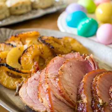 Slices of pineapple glazed ham sits on a platter next to the roasted pineapple slices. A tray of colorful Easter eggs sits in the background.