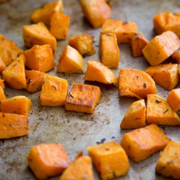 A metal baking sheet has chopped and roasted sweet potatoes scattered on it.