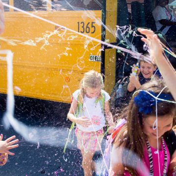Kids coming off a school bus are getting sprayed with silly string by their parents.