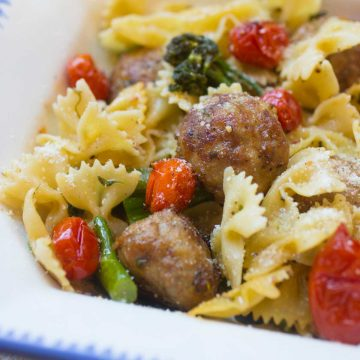 Bow tie pasta is tossed with roasted broccolini, roasted tomatoes, and chicken meatballs.