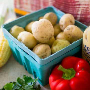 A blue farmer's market carton holds little white potatoes next to a red pepper, ear of corn, and package of bacon.
