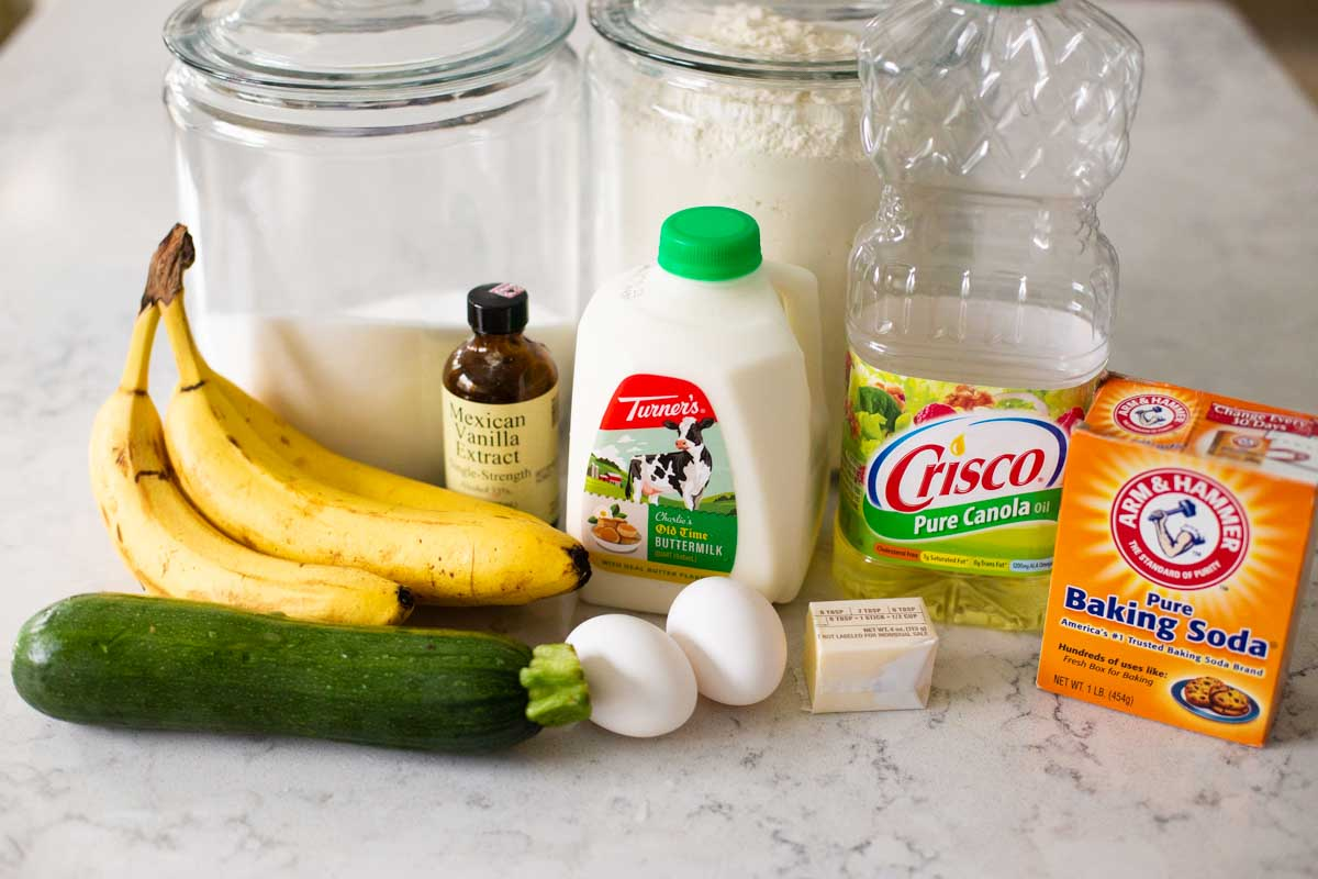 The ingredients for banana zucchini bread sit on a counter.