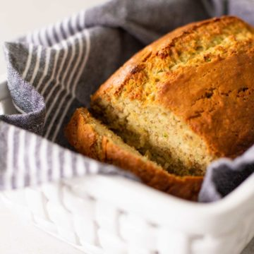 Homemade banana zucchini bread has been sliced to show the inside and sits in a white ceramic bread basket with a grey striped napkin.