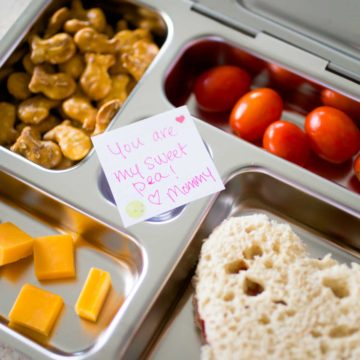 A bento lunchbox has finger foods and a love note from mom for a Kindergartener.