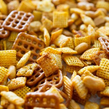 Sweet and spicy honey sriracha chex mix has square pretzles, cereal, and peanuts mixed together.
