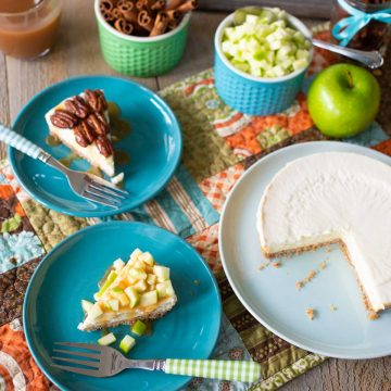 A plain cheesecake has been cut into two slices: One has pecans and caramel, the other has fresh apples and caramel.