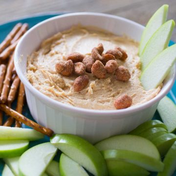 A serving bowl has creamy peanut butter apple dip and is topped with salted peanuts. There are green apple slices in the dip and on the plate with pretzels.