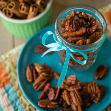 A mason jar filled with spiced pecans has a blue ribbon tied around it and sits on a blue plate with more pecans sprinkled around.