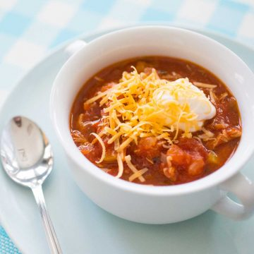 A white bowl of tomato-based chicken chili has shredded cheddar and a dollop of sour cream on top.