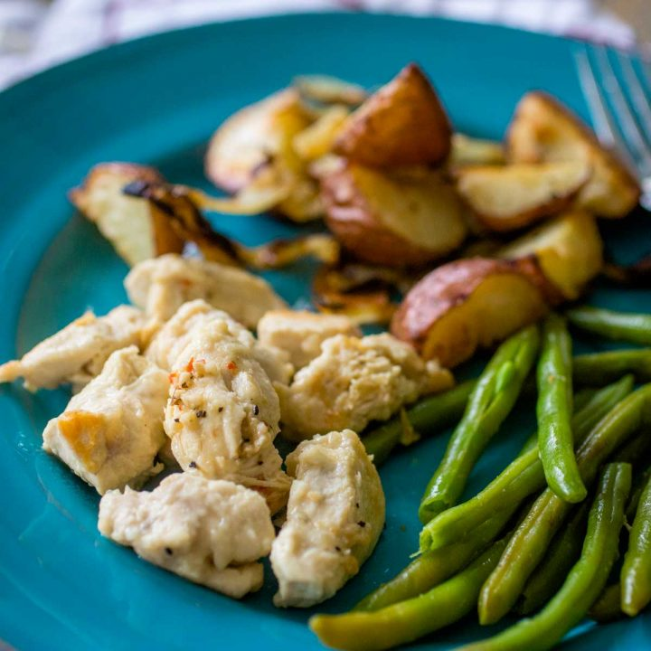 Lemon mustard chicken pieces sit on a blue plat next to roasted potatoes and green beans.