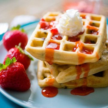 A stack of peanut butter waffles on a blue plate has strawberry jam running down the sides and a dollop of whipped cream on top.