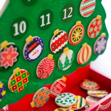 A wooden Advent calendar has colorful painted ornaments hanging on a wooden tree.