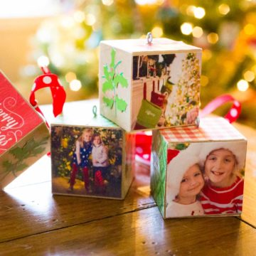 A stack of wooden photo ornaments sits in front of a Christmas tree.