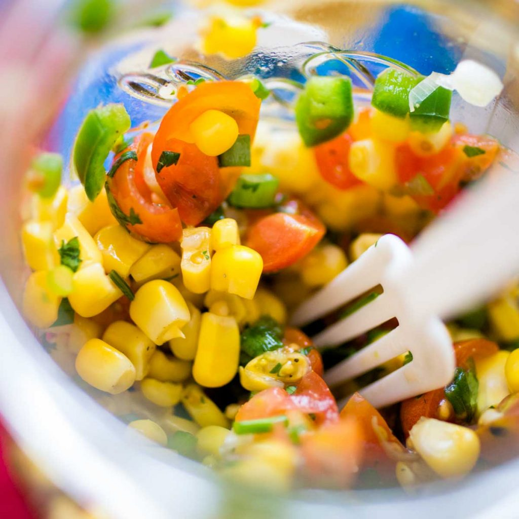 A jar of chunky corn salsa has fresh tomatoes, jalapeno peppers, and cilantro. There's a plastic fork digging in.
