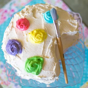 A birthday cake has been decorated to look like a paint palette with a paint brush on the side.