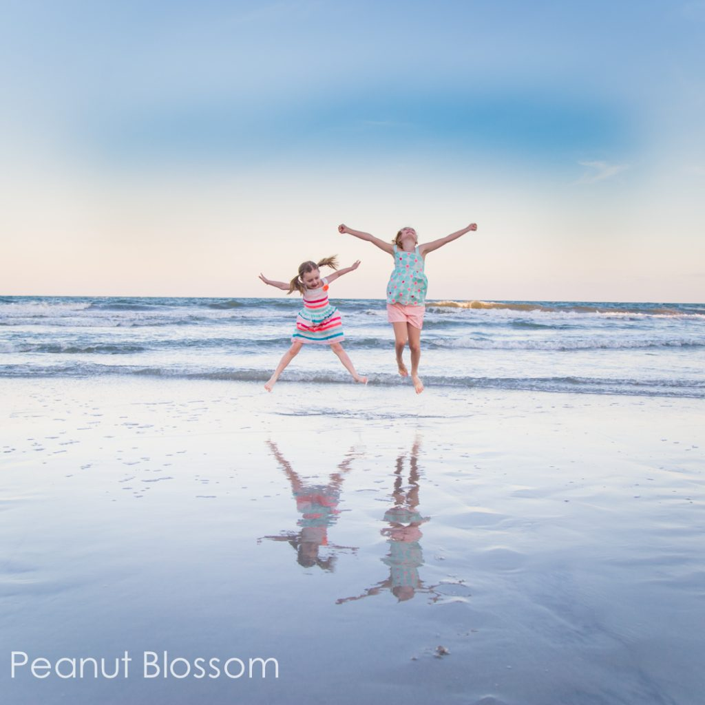 Girls jumping by the water in a beach family photo