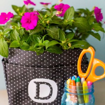 A canvas tote bag with a blooming plant inside.