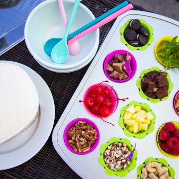 A muffin tin is filled with all different sundae bar toppings including chopped nuts, brownies, cherries, cookies, and fresh mint.