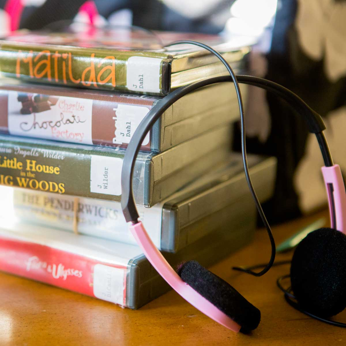 A stack of audiobooks from the library with a pair of pink headphones.