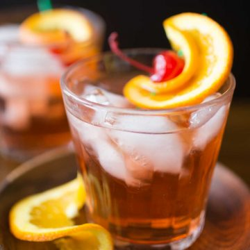 A glass of brandy old fashioned sweet has lots of ice and a maraschino cherry with orange twist for garnish.