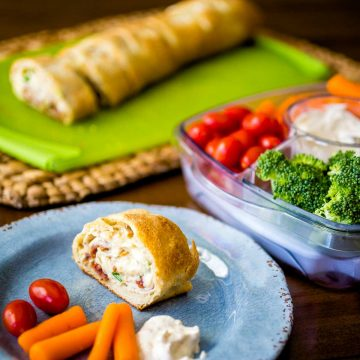 A serving of the chicken cheese roll up sits on a plate next to fresh carrots, tomatoes, and a veggie tray with dip.