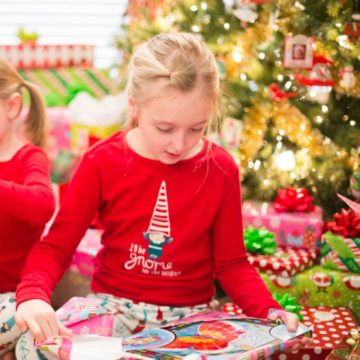 A young girl opens a gift in front of the Christmas tree on Christmas morning.