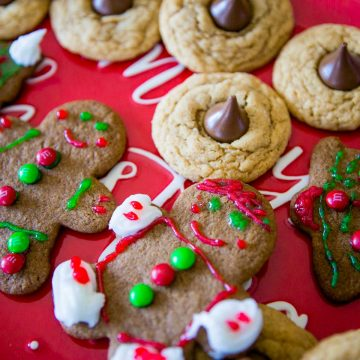 A Christmas cookie platter has frosted gingerbread men and peanut blossom cookies on a red plate.