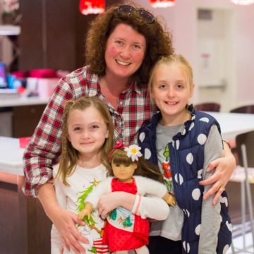 A mom poses with her two daughters during a Christmas Girls Day Out.