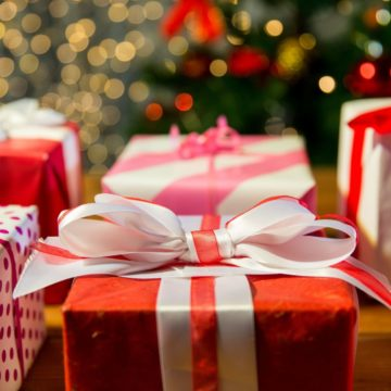 Several Christmas presents are wrapped in red paper with big white satin bows.