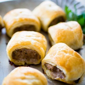 A tray of sausage rolls shows the golden brown puff pastry wrap and savory sausage filling.