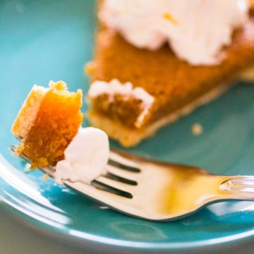 A bite of treacle tart with whipped cream on a fork.
