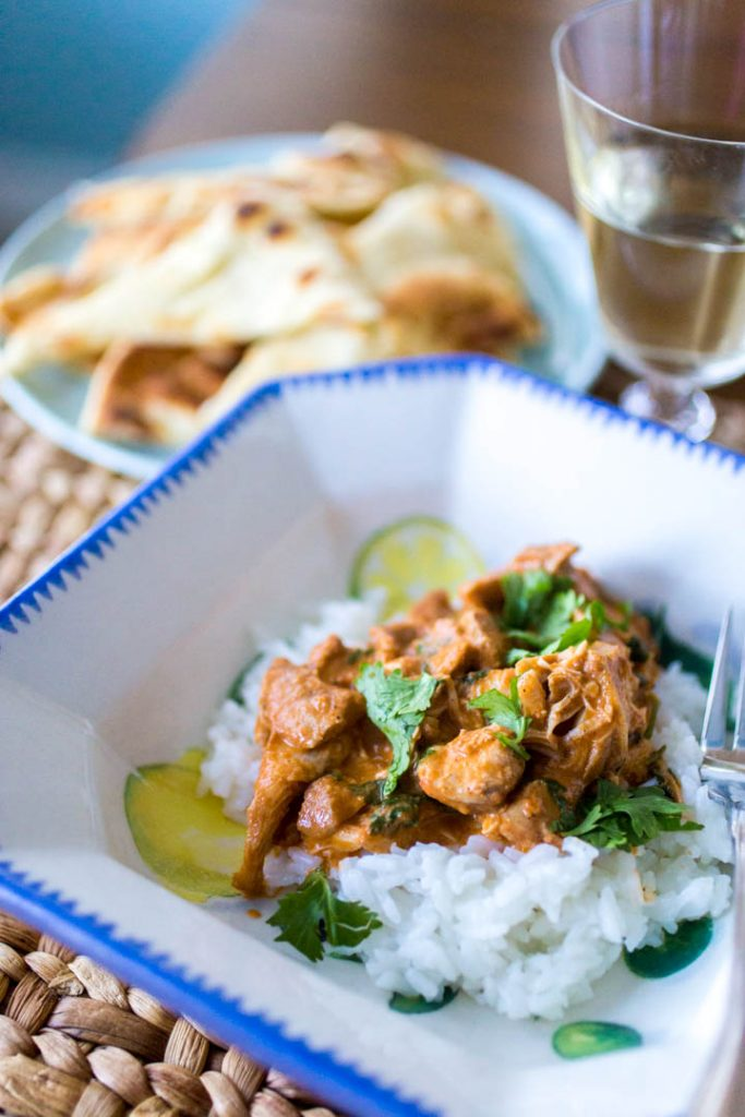 A dish of Indian butter chicken from the Instant Pot is served over jasmine rice with chopped fresh cilantro sprinkled on top.