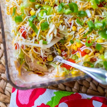 A container of homemade taco dip has a spicy cream cheese filling and is topped with shredded cheese and lettuce. A serving spoon has scooped a portion out.