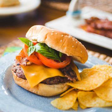 A bacon cheddar burger has layers of fresh tomato and fresh basil and sits next to a serving of potato chips.