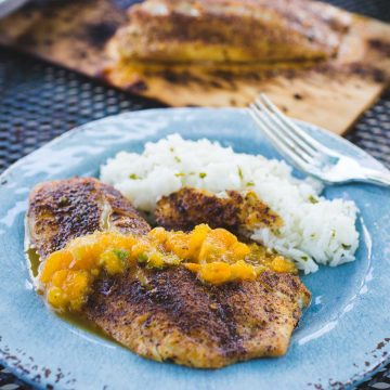 Yellow mojito salsa is drizzled over a spicy grilled tilapia on a blue plate next to a serving of white rice.