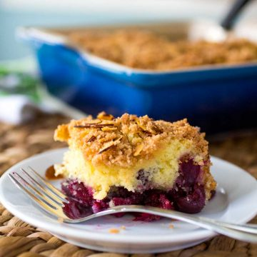 A slice of cherry almond coffee cake shows the layer of big fresh cherries on the bottom and the crumbly streusel topping on top.