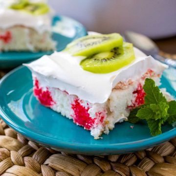 A square slice of strawberry kiwi cake shows the red Jello poke stripes, fluffy whipped topping, and has two thin slices of fresh kiwi on top for garnish.