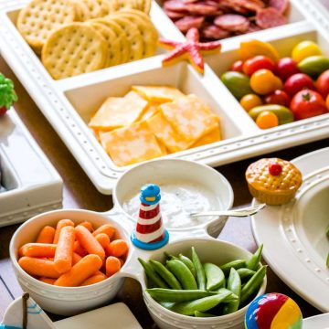 Several trays of party food featuring fresh veggies, cheese, crackers, and meats are laid out on a table.