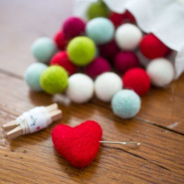 Colorful felt balls are spilling out of a muslin bag.