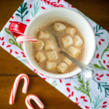 A red mug filled with hot cocoa and mini marshmallows has a candy cane hanging over the edge. Two mini candy canes are on the table and there's a festive holly napkin.