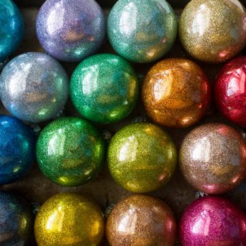 A pile of rainbow glitter ornaments are stacked on a drying tray.