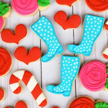 A bunch of Wellie Wishers-themed decorated sugar cookies rest on a table. Blue boots, red hearts, and striped candy cane cookies.