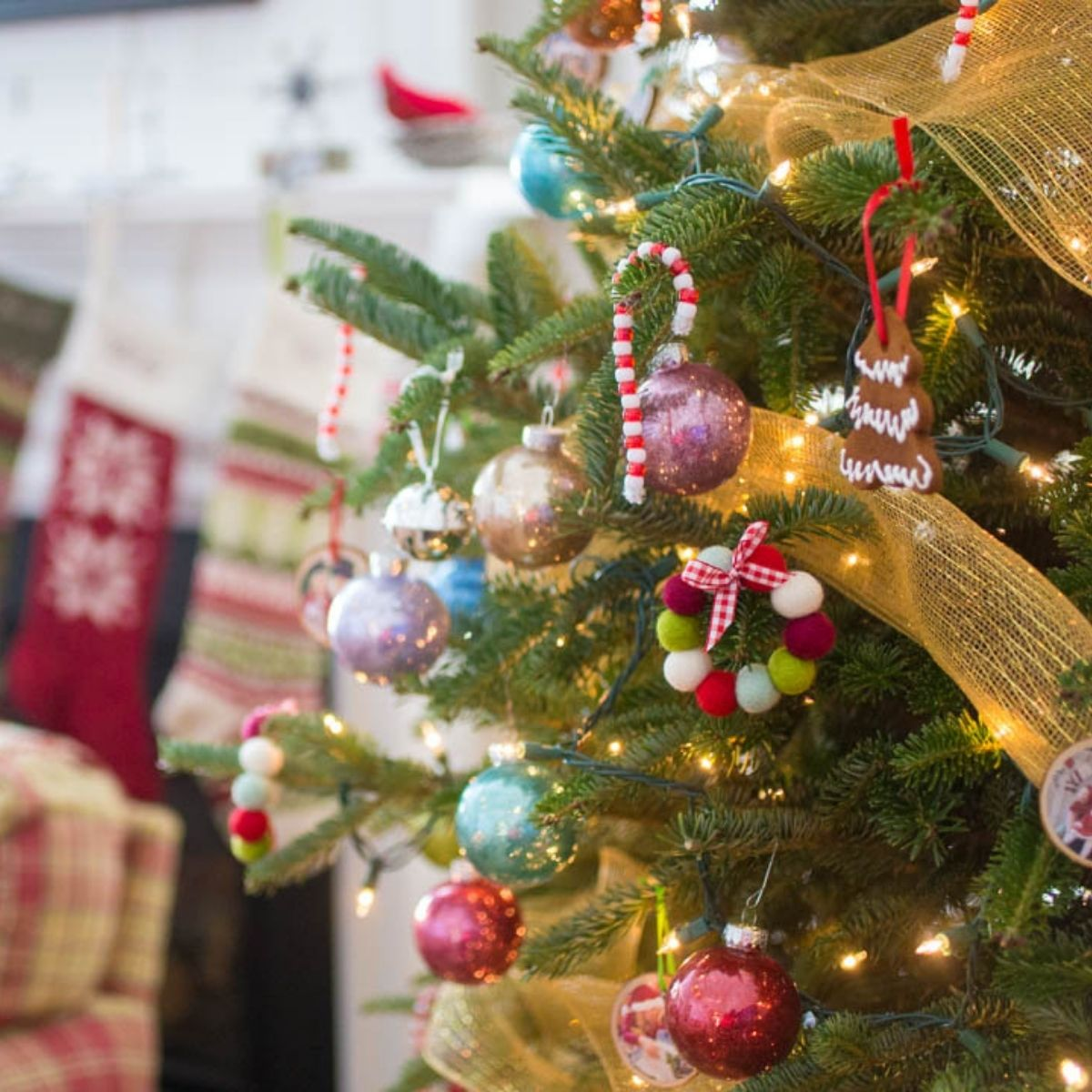 A Christmas tree is decorated with homemade ornaments. You can see stockings in the background.