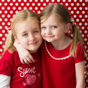 Two young girls wearing Valentine's Day shirts in front of a red and white polka dot background.