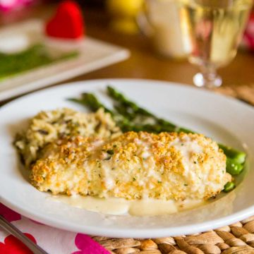 A filet of macadamia encrusted halibut is covered with a drizzle of lemon butter cream sauce. Fresh green asparagus and a serving of wild rice sit next to it on the plate.