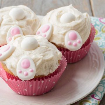 Easter bunny butt cupcakes in pink polka dot wrappers have white frosting and little decorative candies that look like bunny feet, a tail, and ears.