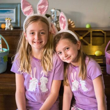 How to take better Easter morning photos of your kids: sisters wearing bunny ears and pastel pajamas sit together on a piano bench.