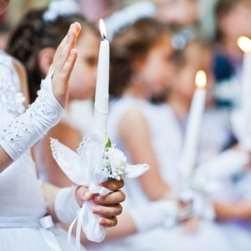 A group of young girls dressed in white dresses holding lit white candles for their First Communion Day.